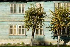 Bäume auf einem Hintergrund eines Holzhauses Stockfoto