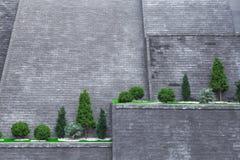 Bäume auf einer hohen Backsteinmauer stockfotos