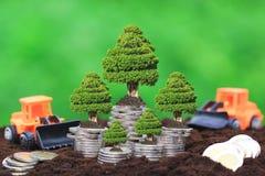 Bäume, die auf Stapel Münzen Geld und LKW-Spielzeug auf natürlichem g wachsen lizenzfreies stockfoto