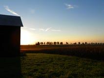 Bäume, Felder und Scheune silhouettiert gegen die untergehende Sonne auf Th Lizenzfreies Stockbild