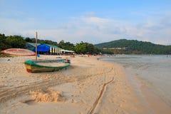 Bäume, Regenschirme, altes Boot und Leute auf Saostrand, Phu Quoc, Vietnam - Dezember 2018 lizenzfreies stockfoto