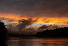 Bäume silhouettiert gegen die brennenden und rauchigen Wolken und das Ende eines Minnesota Seesonnenuntergangs Stockbild