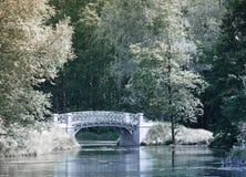 Bäume und die Brücke werden im Fluss, ein Infrarotfoto reflektiert Stockfoto