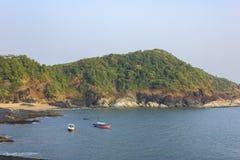 Błękit zatoka z łodziami na wodzie na tle zielony skalisty wzgórze obrazy stock