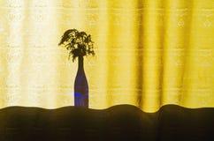 Błękitna Szklana butelka z bukietem kwiaty obrazy stock