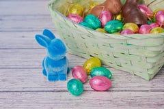 Błękitny Easter królik z czekoladowymi jajkami obok kosza fotografia royalty free