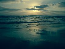 Błękitny zmierzch pod chmurnym niebem na piaskowatej plaży z odbiciami na mokrym piasku obraz royalty free