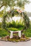Båge för bröllopceremonin Båge som dekoreras med härliga nya blommor och torkduken royaltyfria bilder