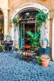 Bågedörringången av cafeterian kallade Caffe Novecento dekorerad med växter och blommor med anseendetabeller och stolar cozy arkivfoto