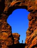 Bågen i kanjon vaggar bildande Silhouetter av fotvandraren arkivbild
