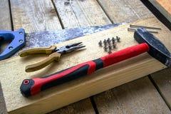 bågfilen plattång, skruvar, hammare, spikar - på en stång och träunplaned bräden Handhjälpmedel för att bygga Arkivfoton