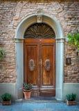Bågingång med den gamla dörren till det Tuscan huset, Italien royaltyfri fotografi
