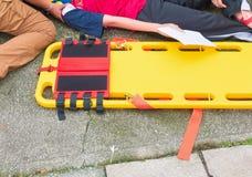 Bårguling och patient som såras för nöd- person med paramedicinsk utbildningserviceskada med medicinsk utrustning i nöd- räddning Fotografering för Bildbyråer