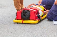 Bårguling och patient som såras för nöd- person med paramedicinsk utbildningserviceskada med medicinsk utrustning i nöd- räddning Royaltyfri Fotografi