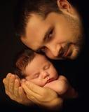 Bébé âgé de peu 15 jours se trouvant solidement sur ses bras du ` s de papa, sur un fond noir Photographie stock libre de droits