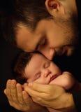 Bébé âgé de peu 15 jours se trouvant solidement sur ses bras du ` s de papa, sur un fond noir Image stock