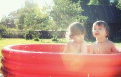 Bébé éclaboussant dans la piscine dehors photos libres de droits