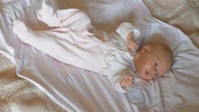 Bébé éveillé d'Active de deux mois sur le lit banque de vidéos