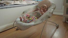 Bébé éveillé et actif dans le siège plein d'entrain à la maison banque de vidéos