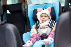 Bébé adorable avec des yeux bleus se reposant dans le siège de voiture L'enfant d'enfant en bas âge en hiver vêtx partir en vacan Photo libre de droits