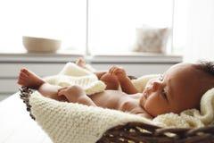 Bébé adorable se situant dans le berceau en osier par la fenêtre photos stock
