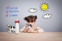 Bébé adorable tenant le verre de lait et dringking le lait photos libres de droits