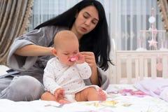 Bébé agité de habillage de mère pendant le matin photos libres de droits