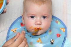 Bébé alimenté par la mâche orange avec la bave-veste image libre de droits