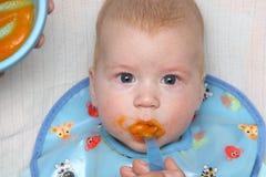 Bébé alimenté par la mâche orange avec la bave-veste ayant la cuillère dans sa bouche photo libre de droits