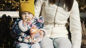 Bébé alimentant par la mère en parc extérieur Sevrage en premières semaines Maman et consommation de l'été d'enfant sur le banc B banque de vidéos