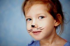 Bébé 3 ans avec la peinture de visage d'un chat, miaulant et souriant regardant l'appareil-photo Photographie stock