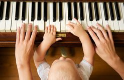Bébé apprenant à jouer le piano avec la mère Photos stock