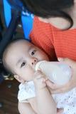 Bébé asiatique avec l'alimentation de lait Image libre de droits