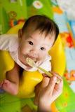 bébé asiatique de 6 mois étant alimenté la céréale Images libres de droits