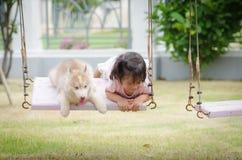 Bébé asiatique de bébé sur l'oscillation avec le chiot Photographie stock libre de droits