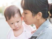 Bébé asiatique de baiser de mère dans le matin Images stock