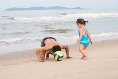 Bébé asiatique et père jouant le football sur la plage Thailan Photographie stock libre de droits