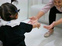 Bébé asiatique marchant vers sa mère, tandis que la mère se penchant en avant avec des mains atteignant prêt à soutenir sa fille Photographie stock libre de droits
