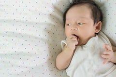 Bébé asiatique mignon s'étendant sur le lit photographie stock libre de droits