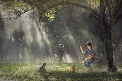 Bébé asiatique sur l'oscillation avec le chiot Photo stock