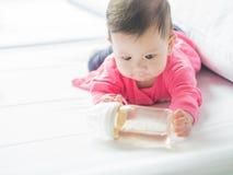 Bébé asiatique tenant la bouteille à lait Photo stock