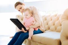 Bébé attentif concentré regardant l'écran d'un comprimé Image stock