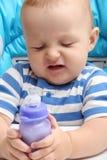 Bébé avec la bouteille à lait malheureuse photo stock