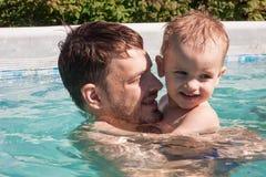 Bébé avec la natation de papa dans la piscine photographie stock
