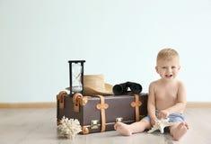 Bébé avec la valise de voyage à la maison photo libre de droits
