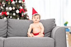Bébé avec le chapeau de Santa et arbre de Noël derrière elle Photographie stock libre de droits
