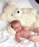 Bébé avec le grand ours de nounours blanc à la maison Image stock