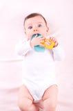 Bébé avec le jouet de teether de hochet Photographie stock