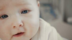 Bébé avec le visage haut étroit d'yeux bleus banque de vidéos