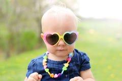 Bébé avec les lunettes de soleil en forme de coeur dehors images stock